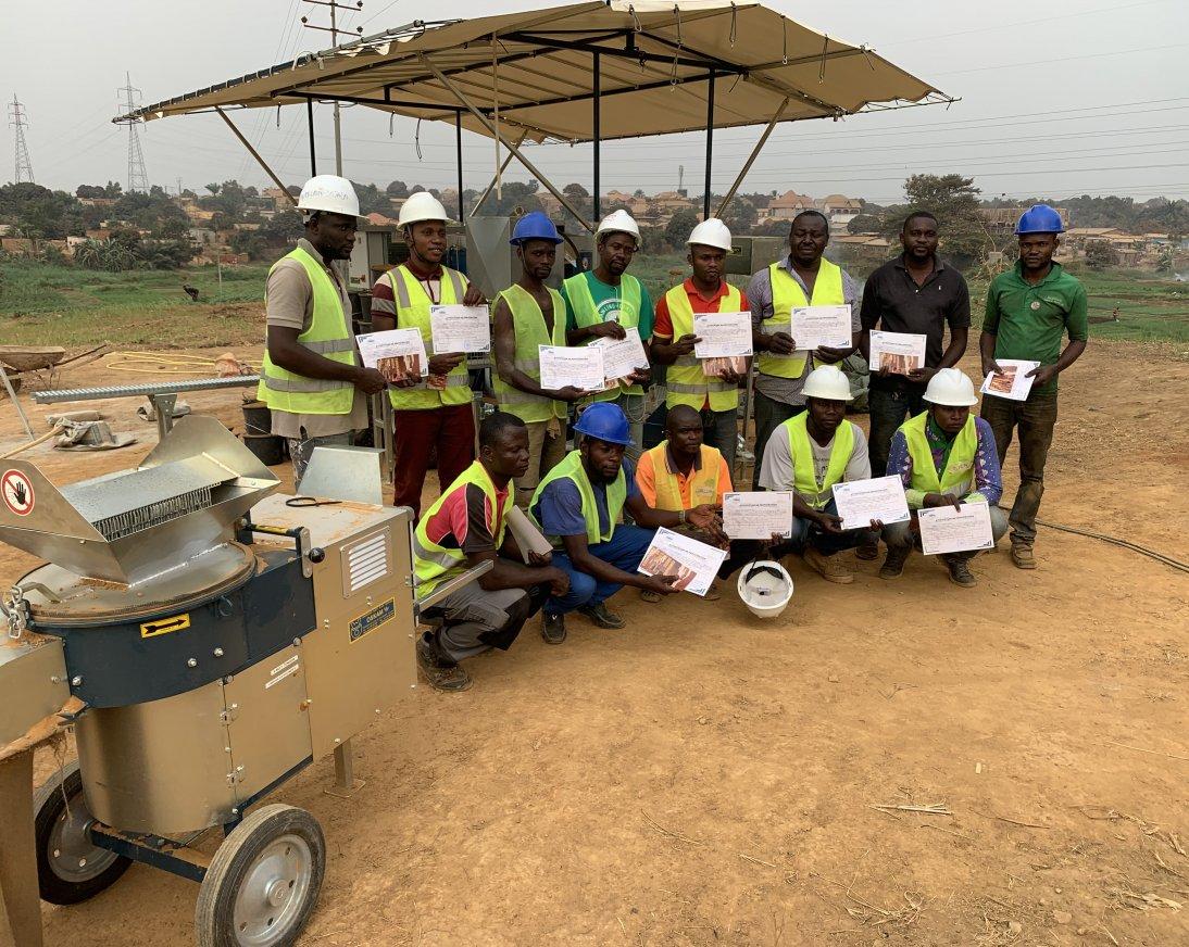 Aquí puede ver personas que han recibido un certificado y están parados frente a una máquina de bloques de tierra comprimida.