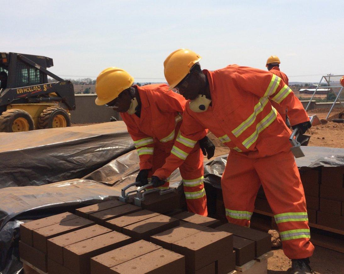 Mannen in een droog landschap aan het werk met compressed earth blocks om uiteindelijk een goed en stevig gebouw te bouwen.